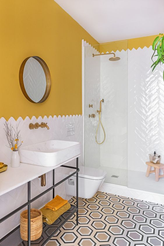 bathroom, white wall tiles on shower area, white top table with white sink, yellow wall, hexagonal floor tiles