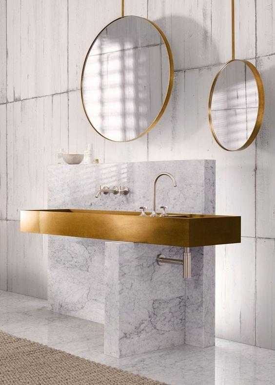 bathroom, white wall, white marble vanity, long golden sink, round mirror wth golden frame
