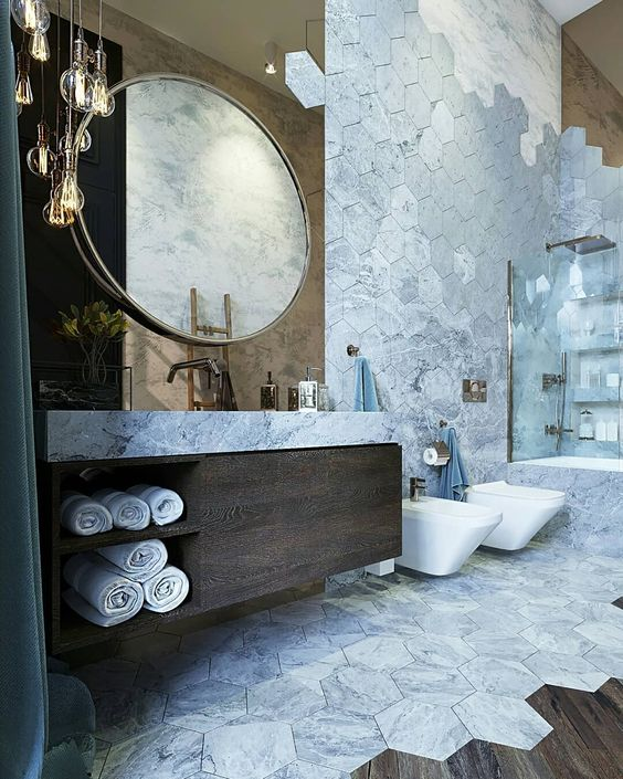 bathroom, wooden floor, white marble hexagonal tiles, wooden vanity cabinet, white marble counter top, golden accent wall, round mirror, glass pendants