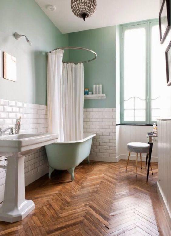 bathroom, wooden herringbone floor tiles, white wall tiles, green wall, green tub, white sink