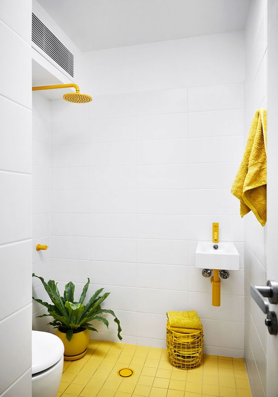 bathroom, yellow floor tiles, white square wall tiles, white floating sink with yellow faucet, yellow shower faucet, white toilet, yellow pot