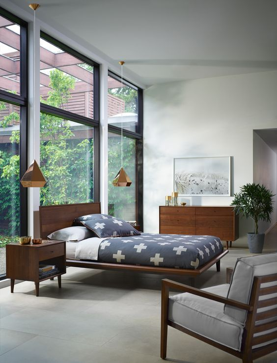 bedroom, grey floor, grey wall, golden pyramid sconce, wooden bed platform, wooden side table, wooden cabinet, wooden chair with grey cushion, glass window