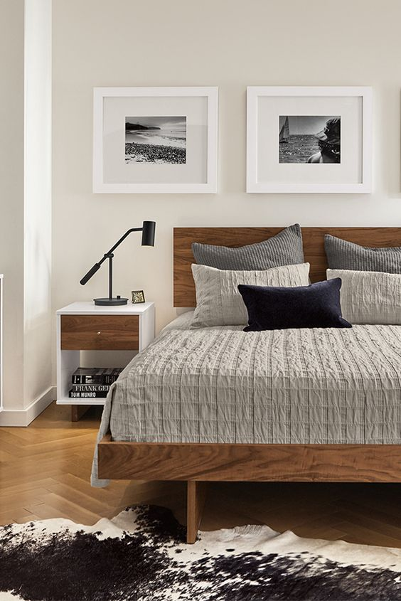 bedroom, wooden floor, white wall, wooden bed platform, grey bedding, white side table, black table lamp
