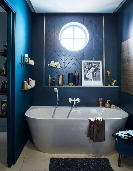 blue bathroom, white tub, blue accent wall, floating shelves, round glass window