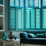 Blue Green Window Shutters, Grey Wall, Wooden Floor, Blue Sofa, Round Coffee Table