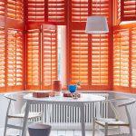 Bold Orange Window Shutter, White Pendant, White Round Dining Table, White Chairs, White Wooden Floor, White Patterned Rug