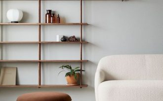 brown wooden shelves, white wall, ceiling mounted, hite marble floor, white sofa, brown ottoman, brown rug