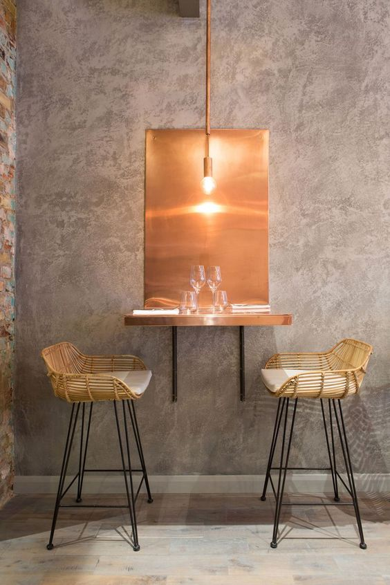 copper floating mounted table, copper pendant, rattan stool, white cushion, grey wall