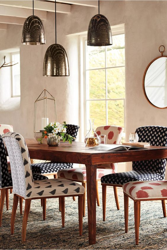 dining room, patterned rug, beige wall, silver pendants, patterned cushioned chairs, wooden table, mirror