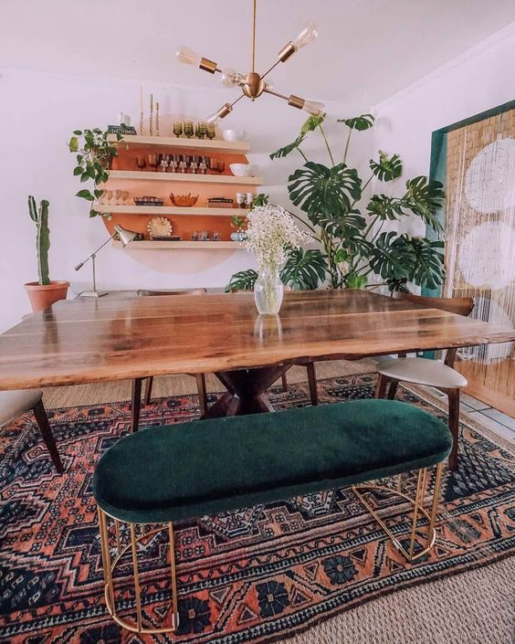 dining room, wooden floor, rug, wooden table, wooden chairs, metal bench green velvety bench, floating shelves, golden pendant
