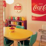 Dining Room, Wooden Floor, White Pink Wall Tiles, Yellow Round Table, Green Chairs, Pendant, Purple Shelves