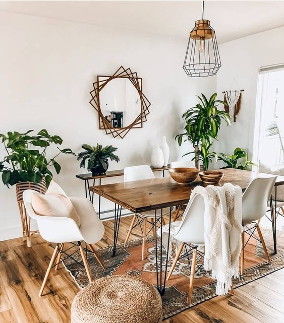 dining room, wooden floor, white wall, metal pendant, mirror, wooden table, white midcentury modern chairs, brown rug,