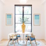 Dining Set, Wooden Floor, White Wall, Pink Patterned Rug, Wooden Chairs With Blue Cushion, White Round Table, Chandelier