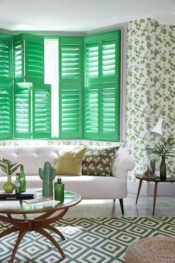 green wooden window shutters, green wallpaper with flower pattern, white marble floor, white sofa, round glass c