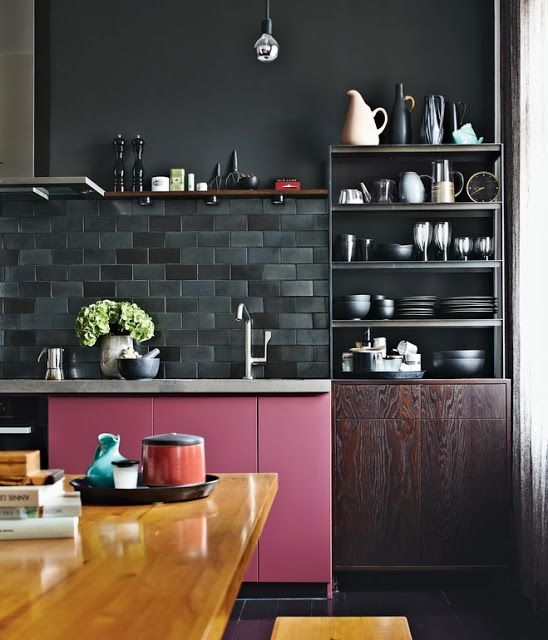 kitchen, black floor tiles, black wall, black subway backsplash tiles, pink bottom cabinet, wooden table, wooden shelves