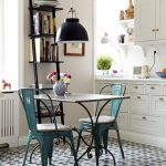 Kitchen, Patterned Floor Tiles, White Wall, White Cabinet, Black Shelves, White Table, Green Vintage Chairs