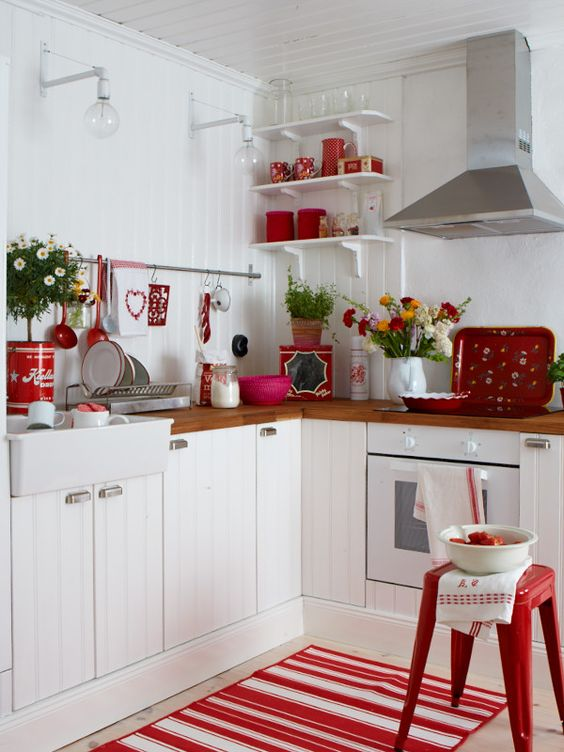 kitchen, white plank wall, white wooden cabinet, wooden counter top, red rug, red stool