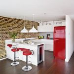 Kitchen, Wooden Floor, White Ceiling, White Pendants, White Island, White Counter Top, Red Stools, Red Fridge, Exposed Wall