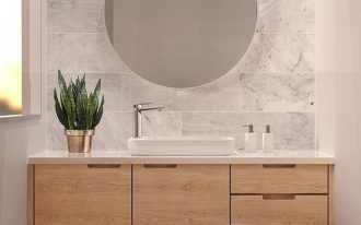 light colored floating cabinet, white marble accent wall, white wall, round mirror, white counter top, white sink, wooden floor