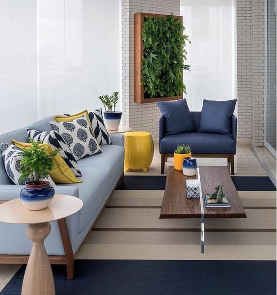 living room, grey brown sriped rug, large glass windows, white brick wallpaper, blue sofa, dark blue chair, wooden coffee table