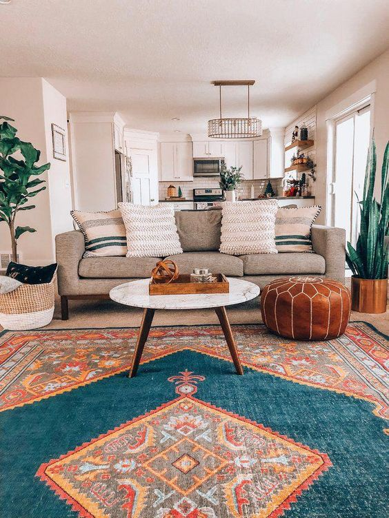 living room, off white wall, brown sofa, round white marble coffee table, brown leather ottoman, patterned rug