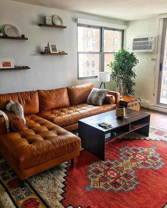 living room, red rug, brown leather sofa, white wall, floating shelves