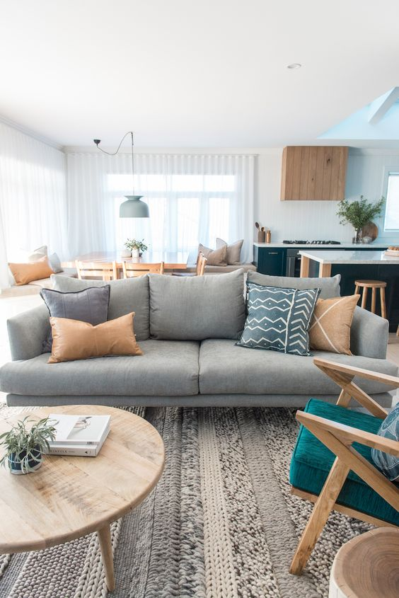 living room, rug, white wall, white ceiling, grey sofa, round wooden coffee table, wooden chair with green cushion
