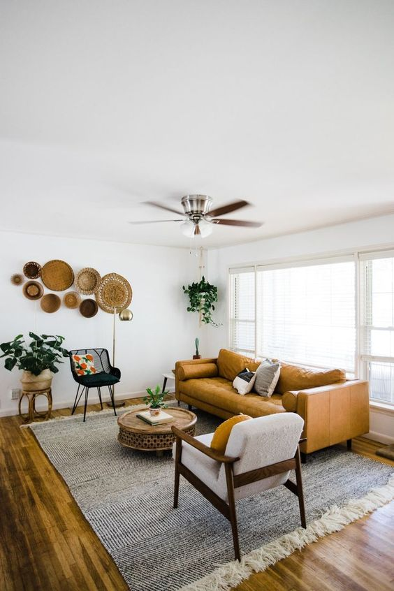 living room, wooden floor, rug, yellow leather sofa, wooden shair, black chair, ceiling fan, round coffee table