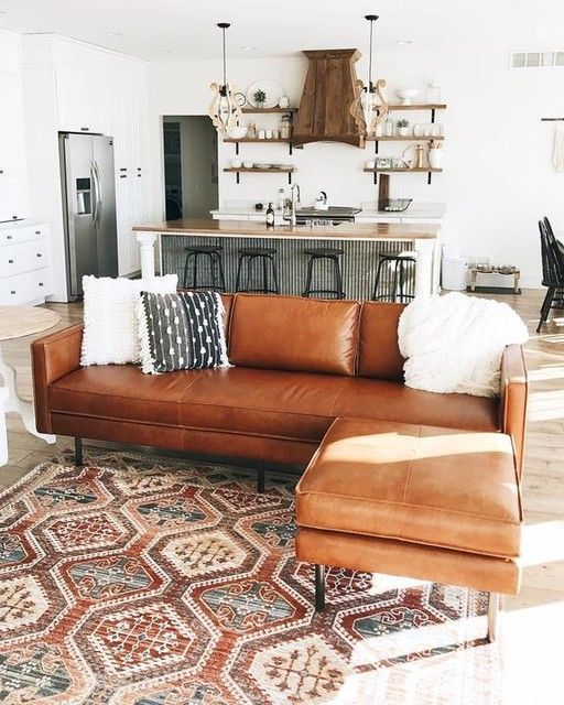 open living room, brown leather sofa, white wall, island with wooden top, patterned rug, interesting pendants