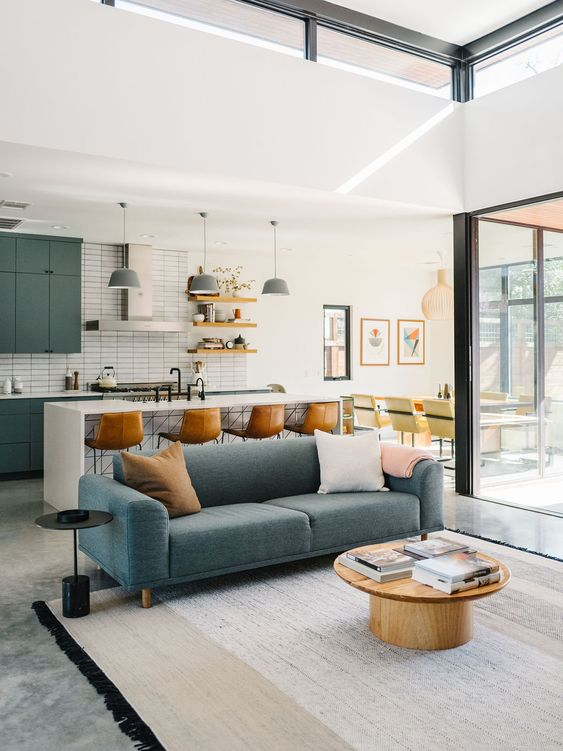 open living room, grey floor, white wall, blue sofa, wooden round coffee table, white subway tiles, rgeeen cabinet