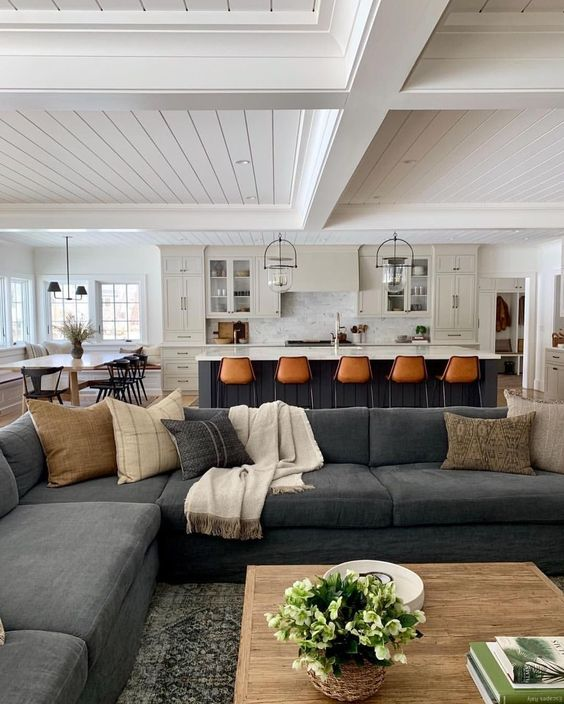 open living room, grey patterned rug, grey sofas, white marble wall, white wooden plank on ceiling, black wooden island, brown stools, white cabinet