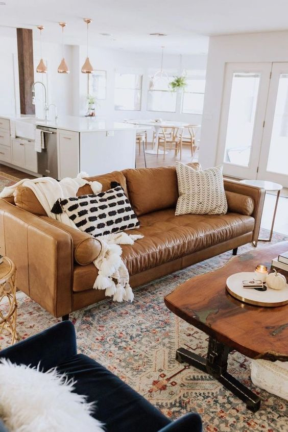 open living room, patterned rug, brown sofa, white wall, wooden coffee table, black chair, golden pendants