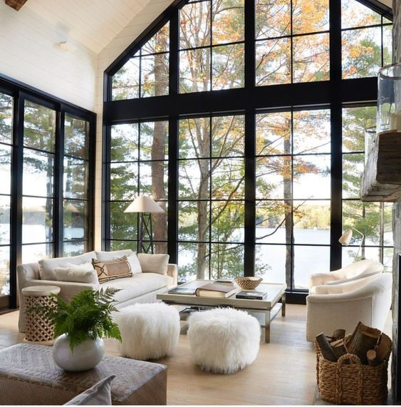 open living room, wooden floor, tall glass windows and wall, white wall, white sofa, white chairs, white ottoman, square coffee table