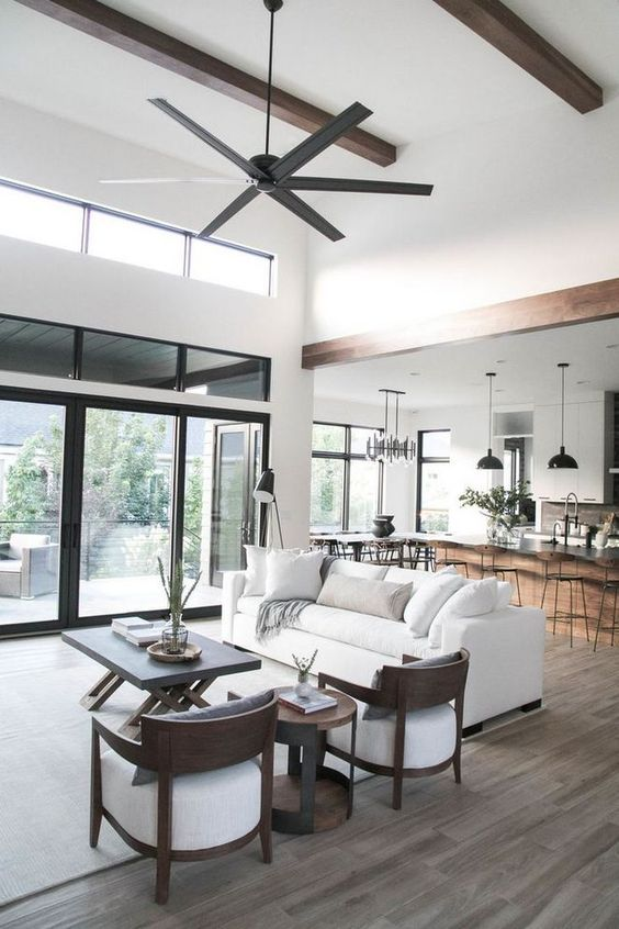 open living room, wooden floor, white ceiling, white wall, white sofa, black coffee table, wooden chairs with white cushion, black ceiling fan