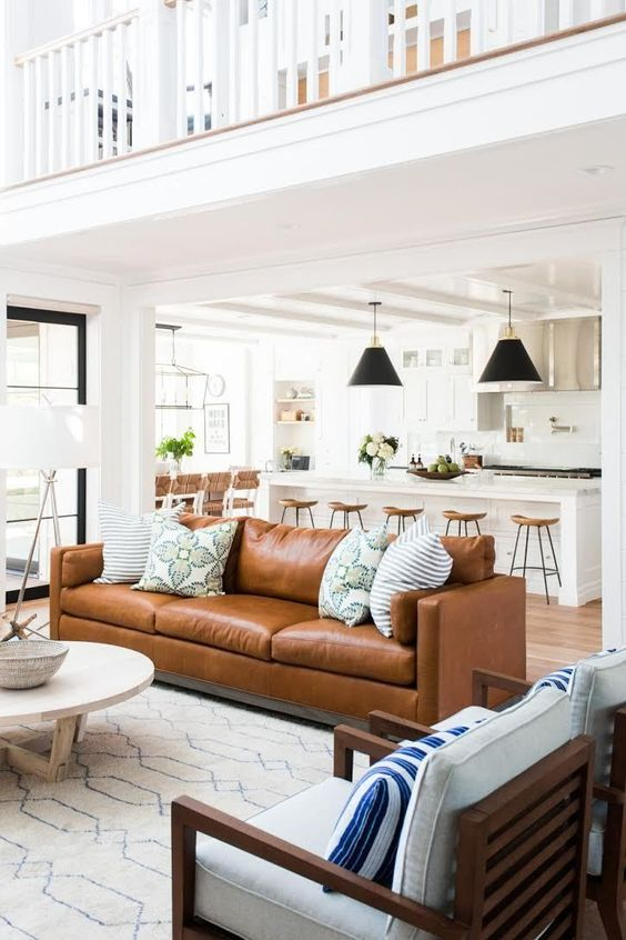 open living room, wooden floor, white island, wooden stools, black pendants, white rug, brown leather sofa, white round table, wooden chairs with white cushion