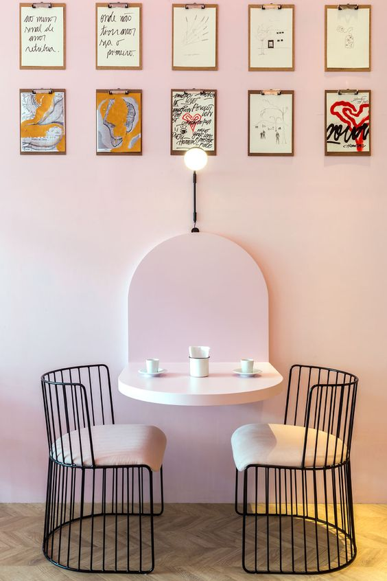 pink mounted floating table, black metal chair with pink cushion, pink wall, wooden wall pattern floor look