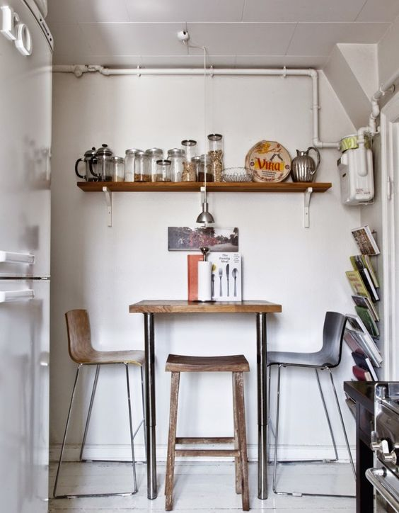 small kitchen, white floor, white wall, floating shelves, wooden tall table, metal stools with wooden seat