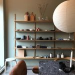 Thin Wooden Shelves, Grey Wall, Grey Seamless Floor, Grey Marble Table, Brown Leather Chair, White Lantern