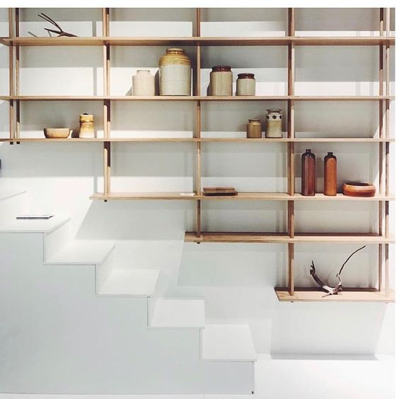 thin wooden shelves, white wall, white stairs,