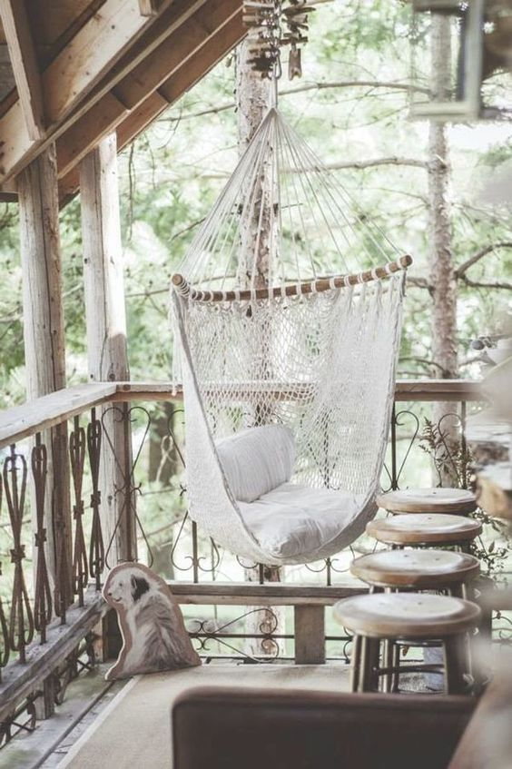 white cloth hammock chair, wooden floor, wooden stools, balcony