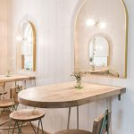 Wooden Hal Round Table, Wooden Chairs With Metal Support, White Wall, Mirror