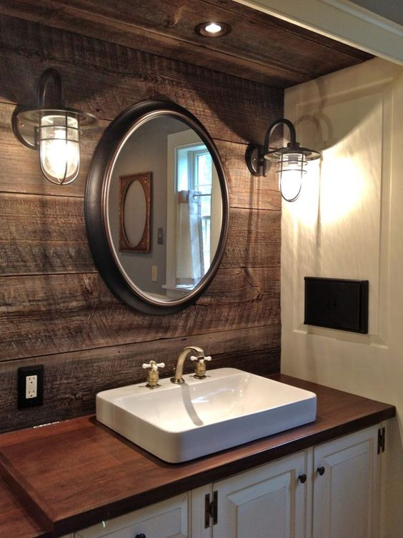 wooden vanity, white vanity cabinet, wooden accent wall, white wall, round mirror, industrial sconces, white sink, wooden counter top