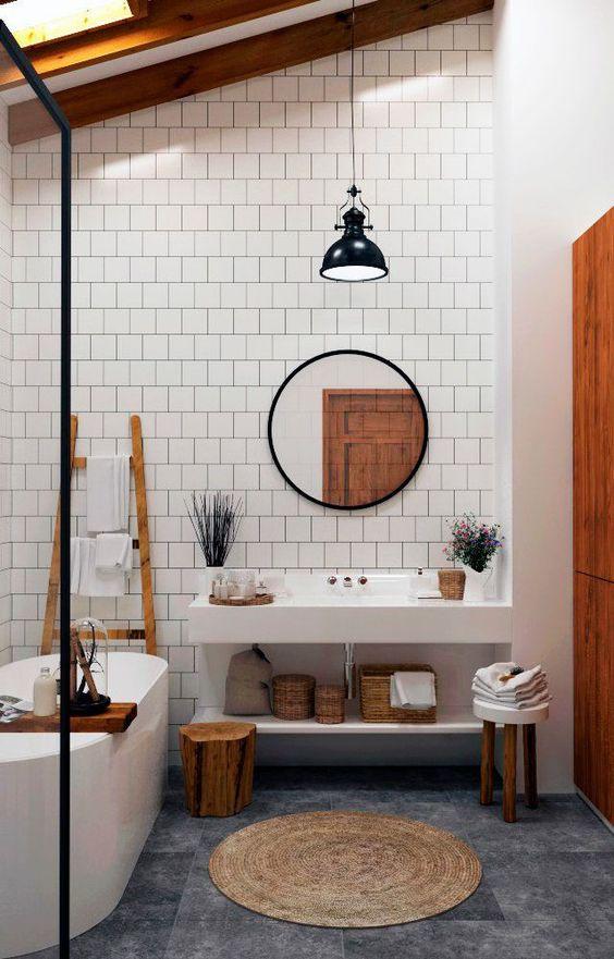 bathroo, grey floor, white wall, white wall tiles, white vanity, white tub, round mirror, black pendant