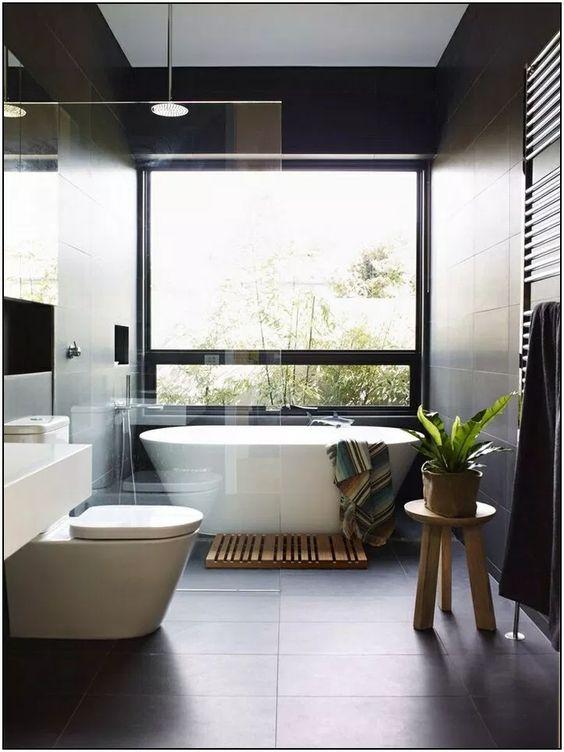 bathroom, black floor, blac kwall, white tub, glass window, wooden stool, white toilet, white vanity