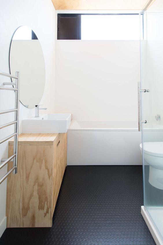 bathroom, black hexagonal floor, white wall, white tub, floating wooden cabinet, round mirror, white toilet
