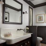 Bathroom, Brick Herringbone Floor, White Wall Tiles, Black Wainscoting, Dark Brown Cabinet, White Long Sink, White Toilet, Black Pendant, Black Framed Mirror
