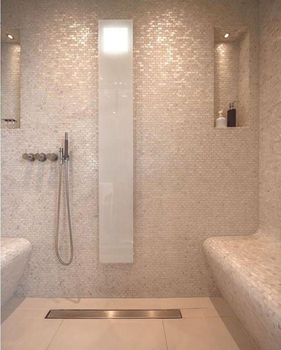 bathroom, cream floor tiles, cream tiny glittery wall tiles, built in bench, indented shelves