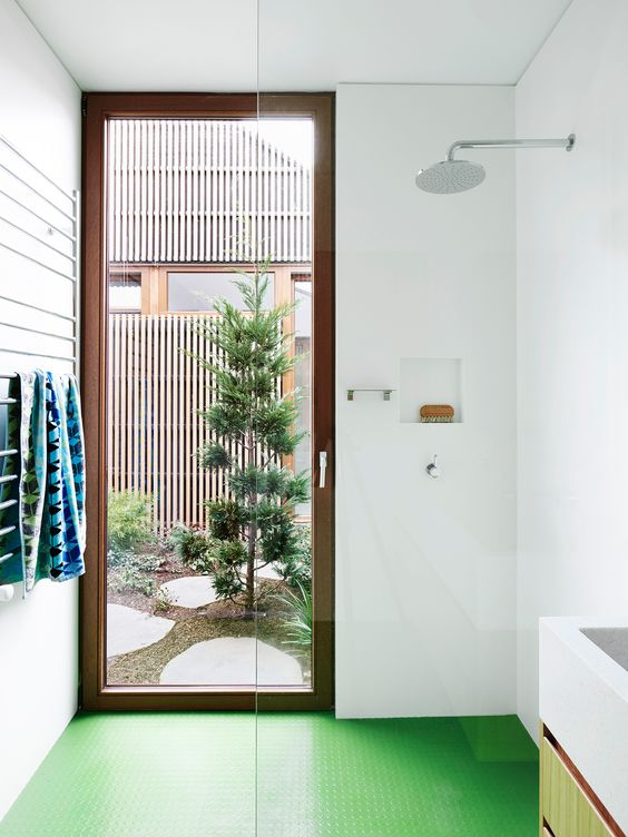 bathroom, green rubber flooring, white wall, white rack, glass partition, glass door, white floating sink