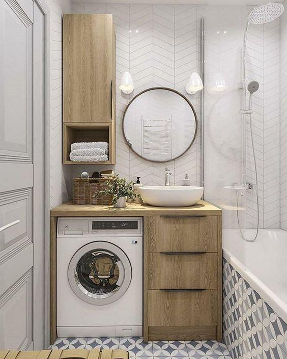 bathroom, grey white patterned floor tiles, white chevron wall tiles, wooden cabinet, white round sink, round mirror, white sconce, white tub