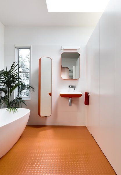 bathroom, orange rubber flooring, white wall, red foating sink, red framed mirror, tall mirror, white tub